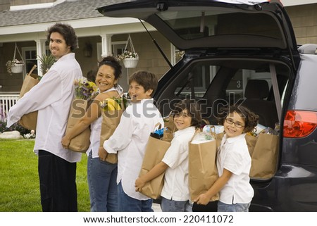 Hispanic family unloading grocery bags from car - stock photo