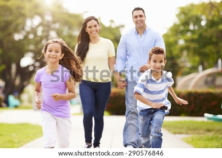 Hispanic Family Walking In Park Together - stock photo