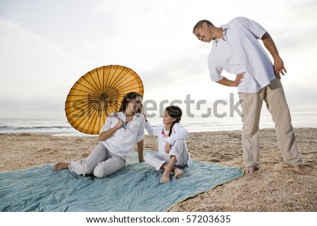 Hispanic family with 9 year old girl on beach blanket - stock photo