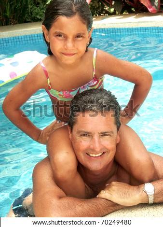 Hispanic father and daughter enjoying a swimming pool. - stock photo