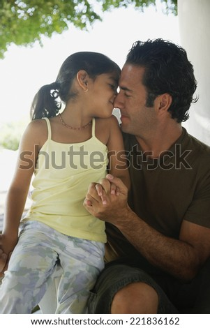 Hispanic father and daughter hugging - stock photo