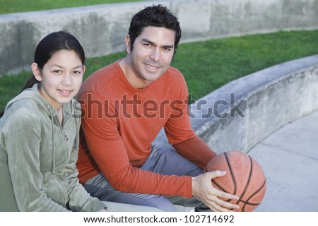 Hispanic father and daughter with basketball - stock photo