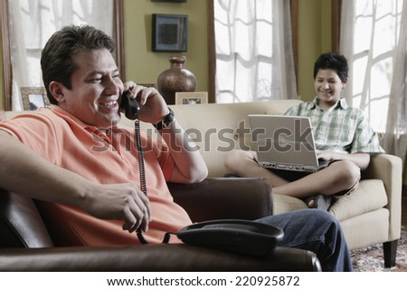 Hispanic father and son relaxing in livingroom - stock photo