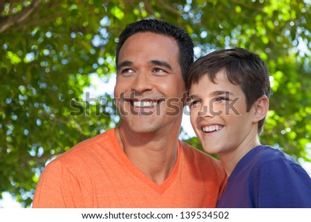 Hispanic father and teenage son happily standing together outside in yard, looking off into distance. - stock photo