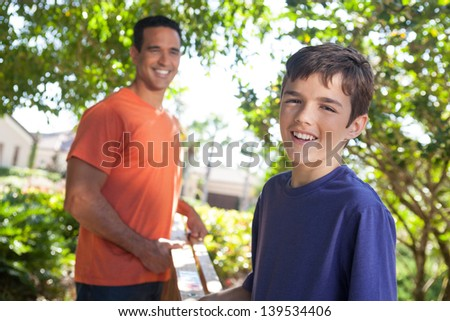 Hispanic father and teenaged son happily carry ladder together outside in yard. - stock photo