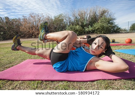 Hispanic female doing abdominal crunches in outdoor exercise class - stock photo