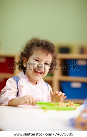 hispanic female preschooler eating pasta and smiling at camera. Vertical shape, waist up, copy space - stock photo