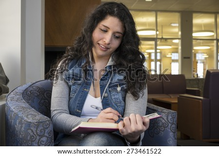 Hispanic female reading a book in the library - stock photo