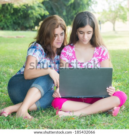 Hispanic girl and her young mother using a laptop computer outdoors