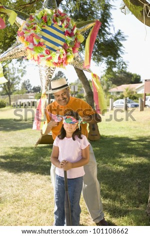 Hispanic girl being blindfolded next to pinata outdoors - stock photo