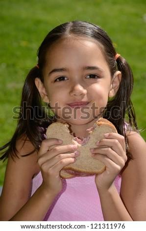 Hispanic Girl Eats a Salami Sandwich. - stock photo