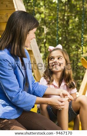 Hispanic girl sitting on playground slide smiling at woman applying first aid bandage to knee. - stock photo