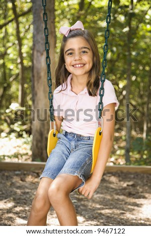 Hispanic girl sitting on swing smiling at viewer. - stock photo