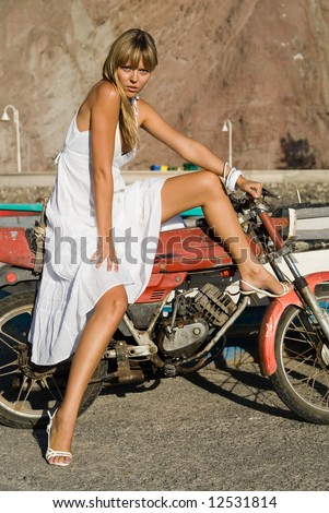 Hispanic girl with a white dress and a motocycle - stock photo