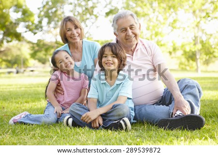 Hispanic Grandmother And Grandfather Relaxing With Grandchildren In Park - stock photo