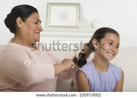 Hispanic grandmother brushing granddaughter's hair