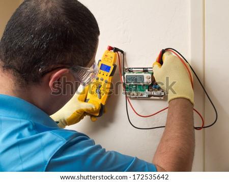 Hispanic handyman repairman conducting residential HVAC repair - stock photo