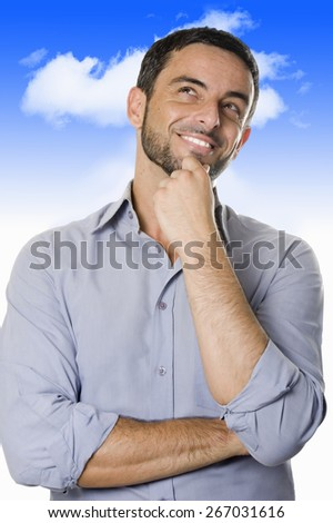 Hispanic happy young man with beard thinking about a project, visualizing in his mind and imagination, considering a decision or having a brilliant idea smiling on a blue sky background - stock photo