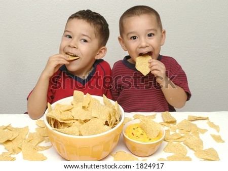 Hispanic kids and tortilla chips - stock photo