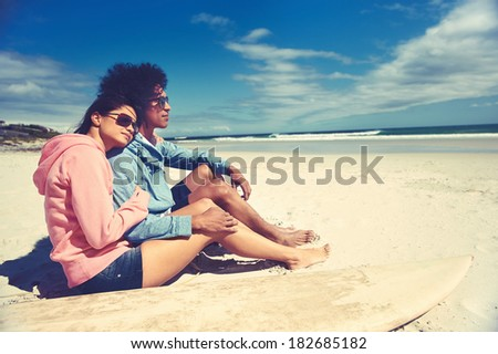Hispanic Latino couple sitting on beach together in love and affection - stock photo