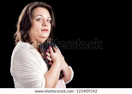 hispanic looking woman in a light dress against a black background holding a bible close to her body as she looks up in thought. Plenty of copy space for your personal text. - stock photo