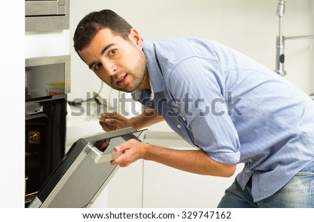 Hispanic male wearing blue shirt in modern kitchen leaning towards open oven door holding a fork looking past camera.