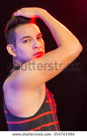 Hispanic male wearing red black striped singlet posing with serious facial expression, showing right arm covering mouth, profile angle. - stock photo