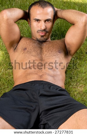 Hispanic man doing a sit up - stock photo