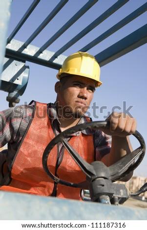 Hispanic man driving bulldozer at construction site - stock photo