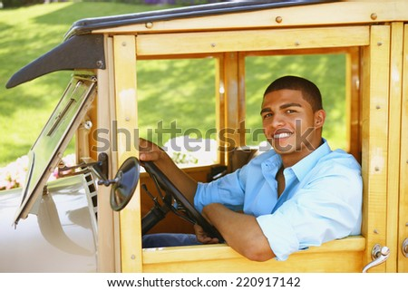 Hispanic man driving old fashioned car - stock photo