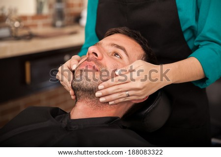 Hispanic man getting a face massage before getting shaved by a lady barber