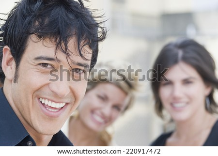 Hispanic man smiling with friends in background - stock photo