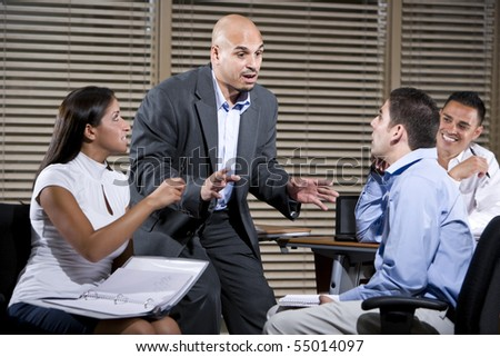 Hispanic manager talking with group of office workers - stock photo