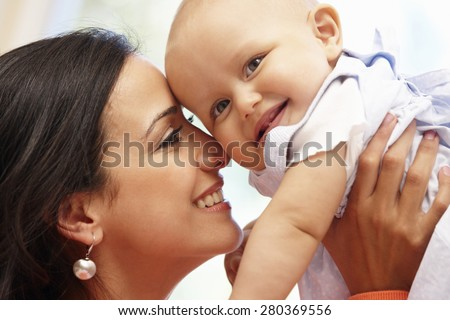 Hispanic mother and baby at home - stock photo