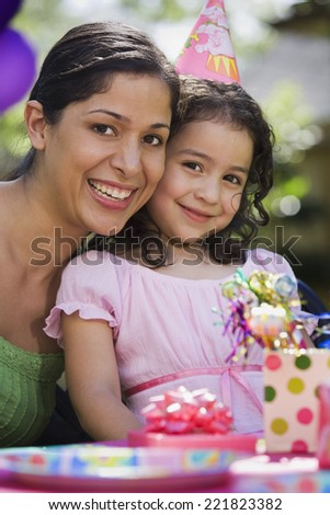 Hispanic mother and daughter at outdoor birthday party - stock photo
