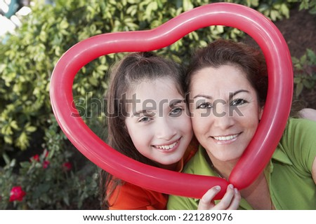 Hispanic mother and daughter holding heart-shaped balloon - stock photo