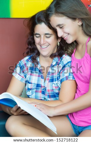 Hispanic mother and her beautiful daughter reading a book at home - stock photo