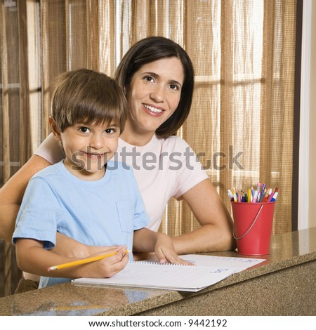 Hispanic mother and son with homework smiling at viewer. - stock photo