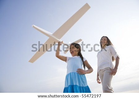 Hispanic mother and 9 year old child having fun with toy plane - stock photo