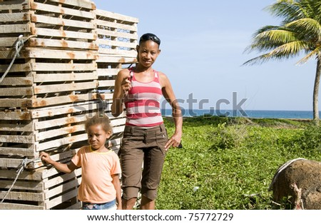 Hispanic mother daughter by lobster pot traps Caribbean Sea Big Corn Island Nicaragua Central America - stock photo