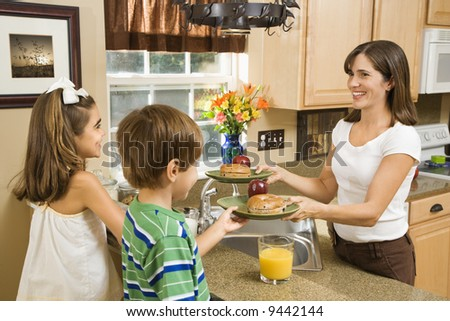 Hispanic mother giving healthy breakfast to young children in home kitchen. - stock photo