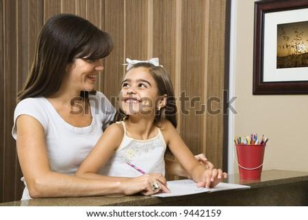 Hispanic mother helping daughter making eye contact and working on homework. - stock photo