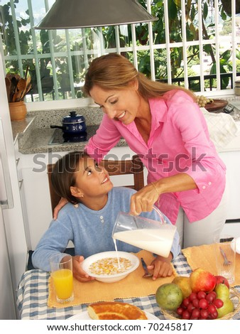 Hispanic mother pouring milk and cereal corn to her daughter. - stock photo