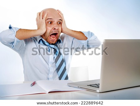 hispanic overworked frustrated businessman on tie screaming in stress at computer laptop working on office worried about financial crisis or making a huge mistake - stock photo