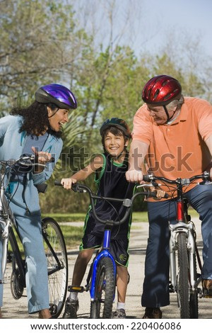 Hispanic parents and son riding bicycles - stock photo