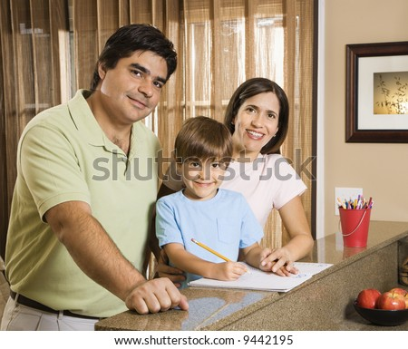 Hispanic parents and son with homework smiling at viewer. - stock photo