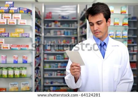 hispanic pharmacist reading prescription at pharmacy - stock photo