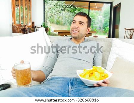 Hispanic pleased male wearing light blye sweater enjoying potato chips and beer sitting in white livingroom sofa facing camera. - stock photo