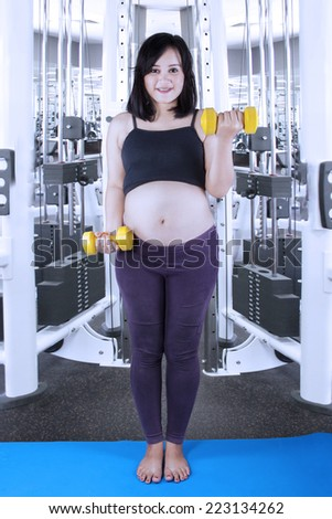Hispanic pregnant woman standing on mattress while workout with two dumbbells - stock photo