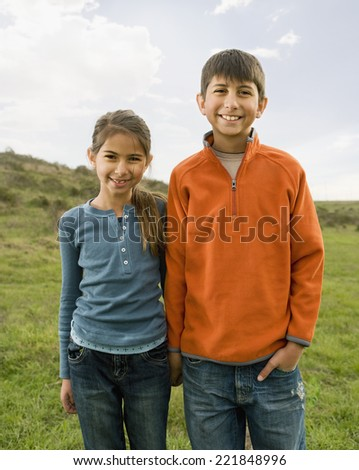 Hispanic sister and brother in field - stock photo
